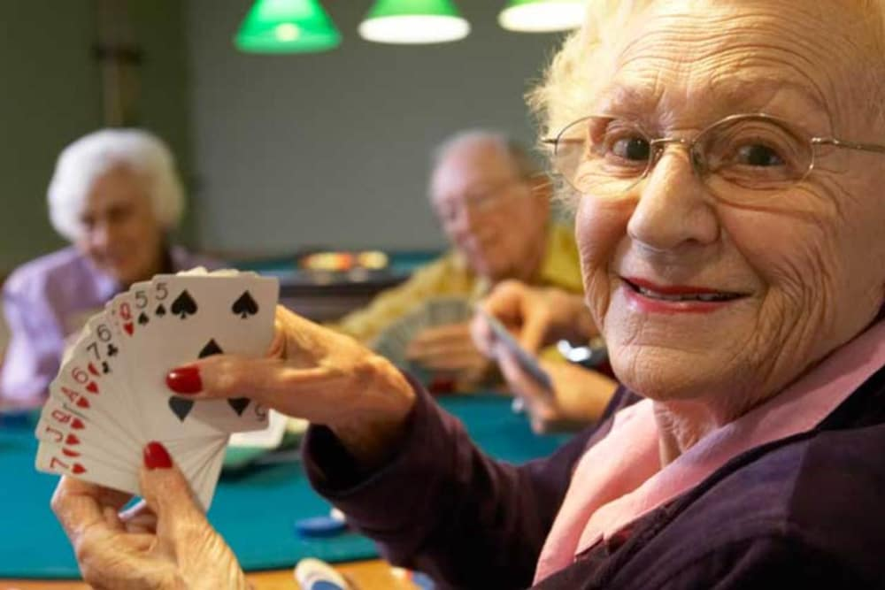 Senior woman smiling about her dealt cards at Ramsey Village Continuing Care in Des Moines, Iowa