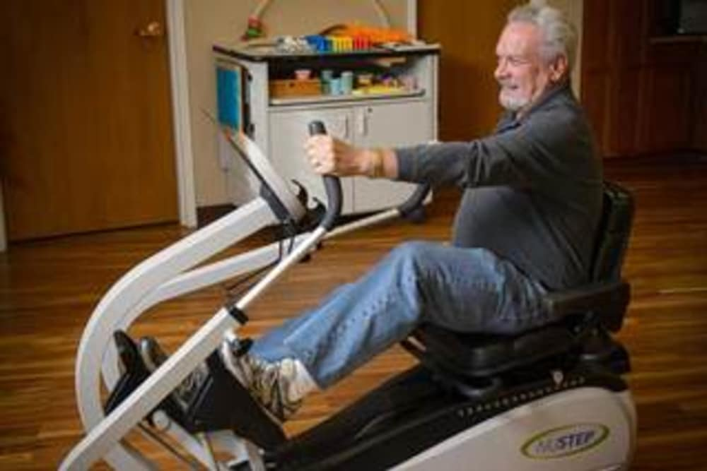 Senior man using an exercise machine at Ramsey Village Continuing Care in Des Moines, Iowa