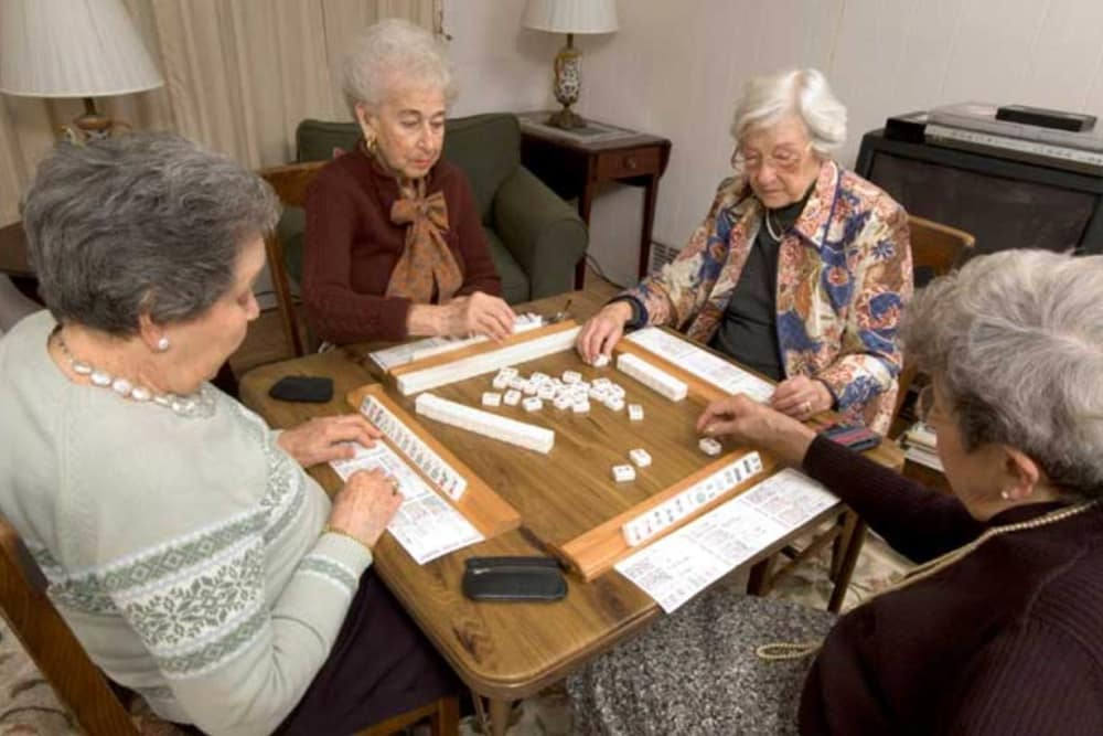 A group of seniors playing dominoes at Inglenook At Brighton in Brighton, Colorado