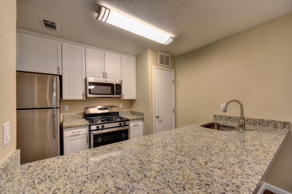 Naturally well-lit kitchen with granite counter tops at Antelope Vista in Antelope, California