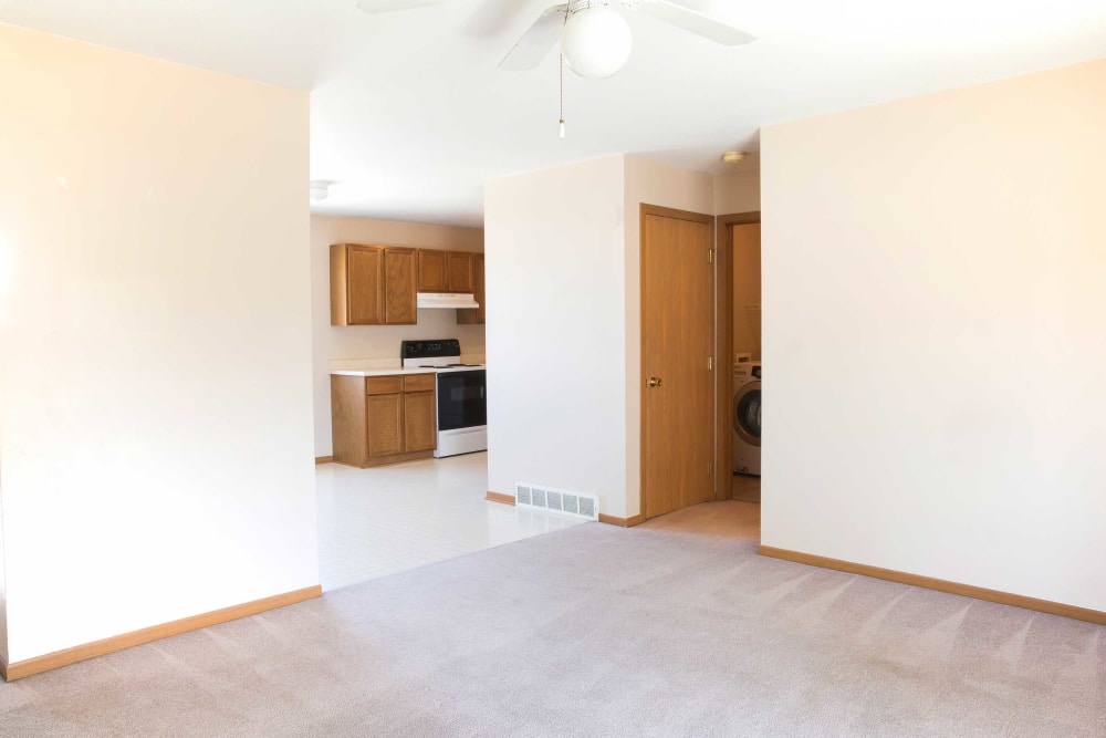 Carpeted living room leading to the laundry room at Crown Point Apartments in Ames, Iowa