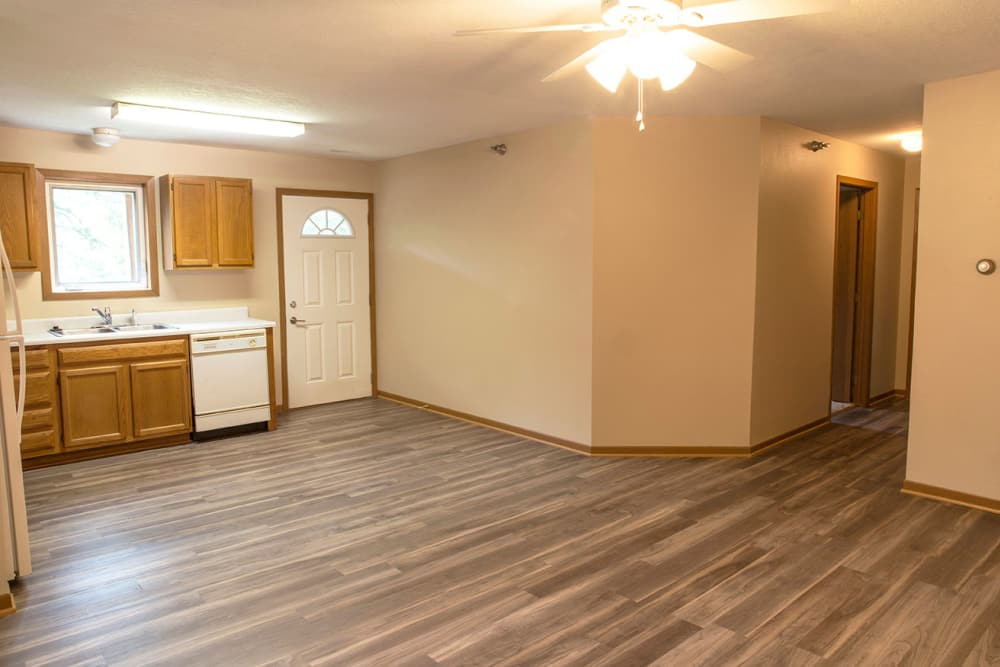 Kitchen and dining room with wood flooring at Stone Court in Ames, Iowa