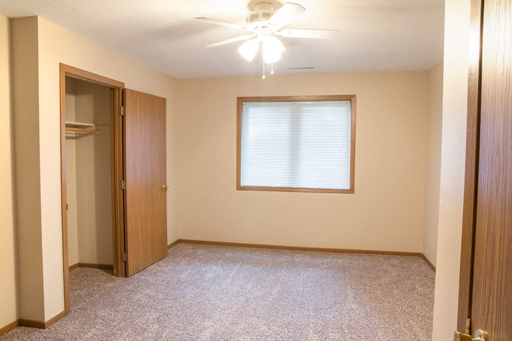 An apartment bedroom with a window and closet at Stone Court in Ames, Iowa