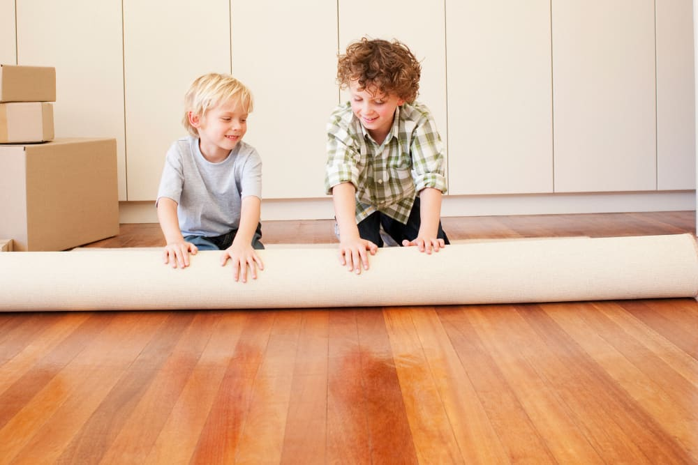 Children rolling up a rug