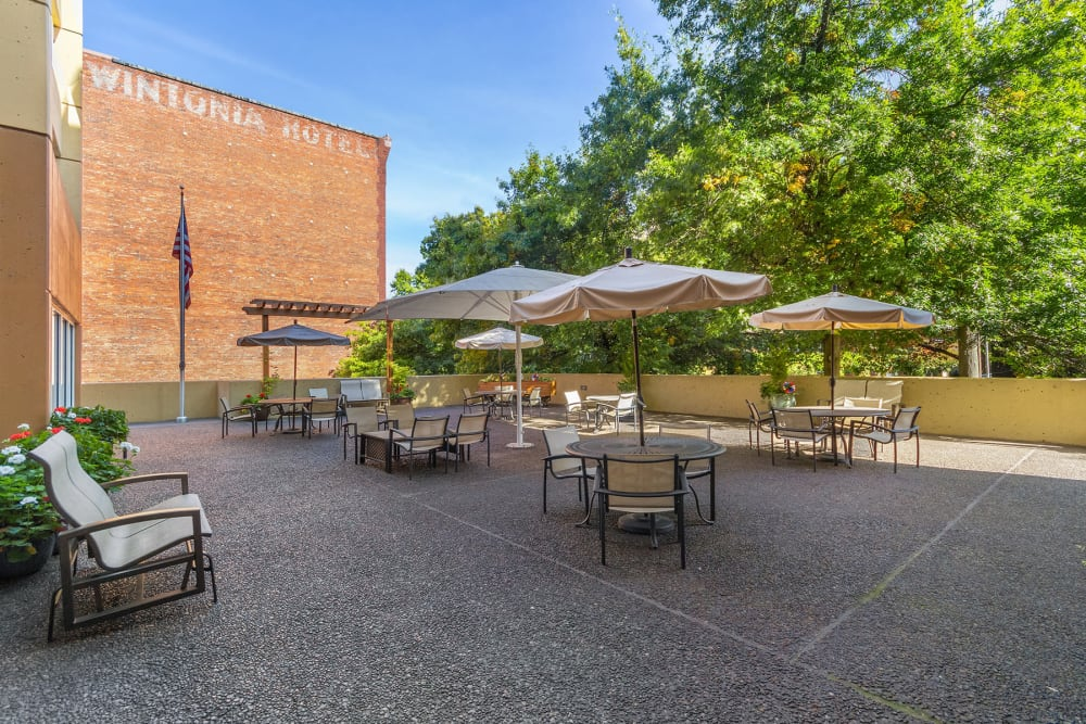 Back patio area with umbrella tables at our senior living community in Seattle, WA