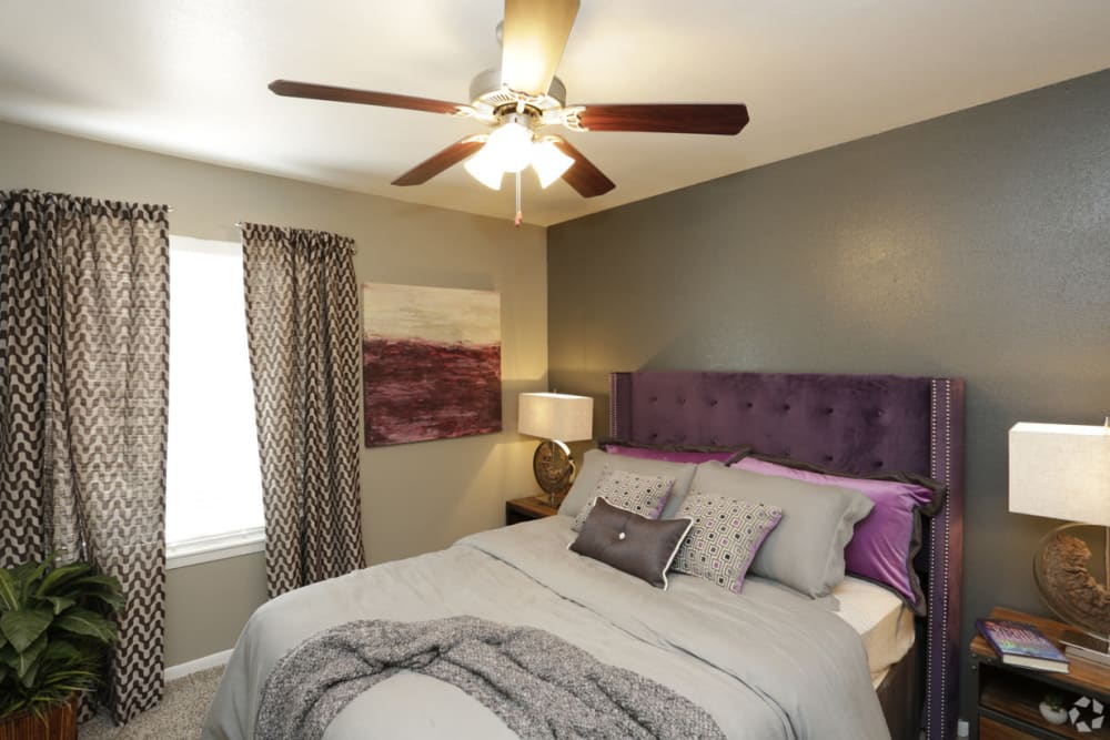 Cozy bedroom with ceiling fan at EnVue Apartments in Bryan, Texas