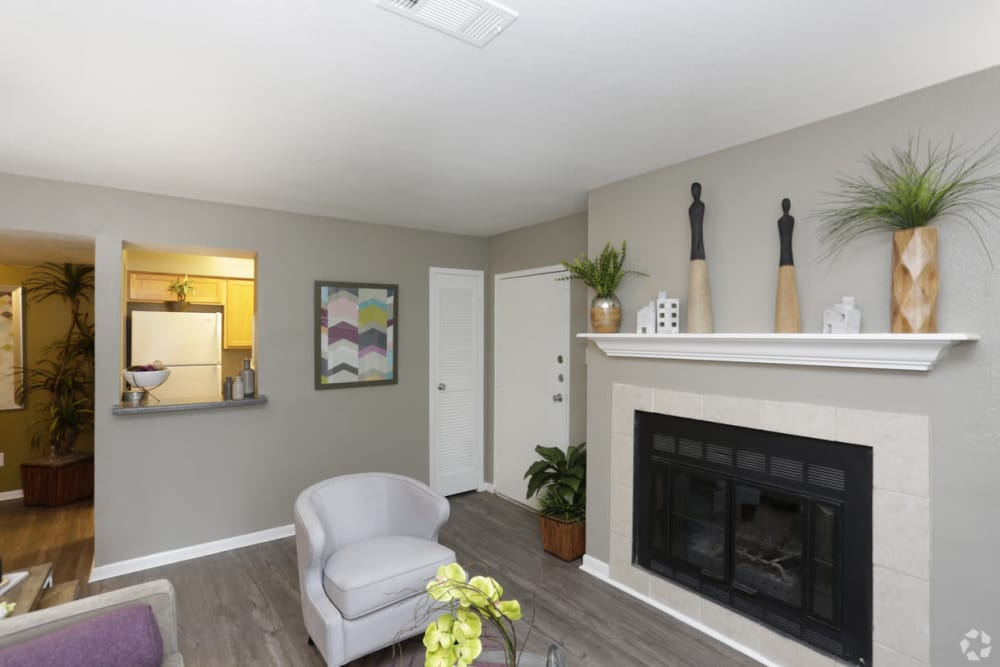 A great-for-entertaining living room with a fireplace at EnVue Apartments in Bryan, Texas