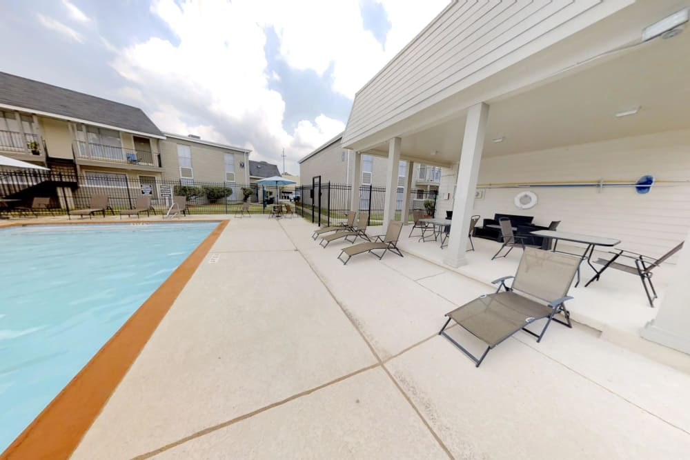 Covered sitting area next to the sparkling pool at Northlake Manor Apartments