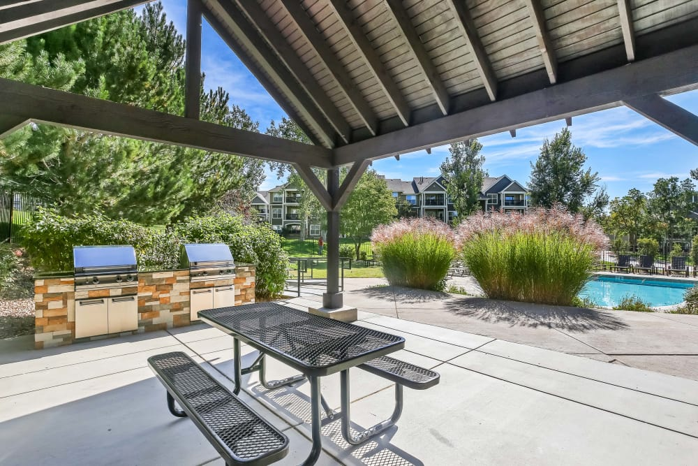 Open outdoor seating and grill area at The Pines at Castle Rock Apartments in Castle Rock, CO