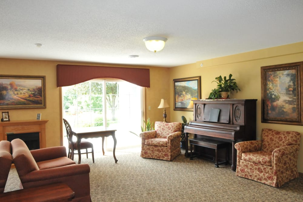 Living room with comfortable seating and a piano at The Glenn Buffalo in Buffalo, Minnesota