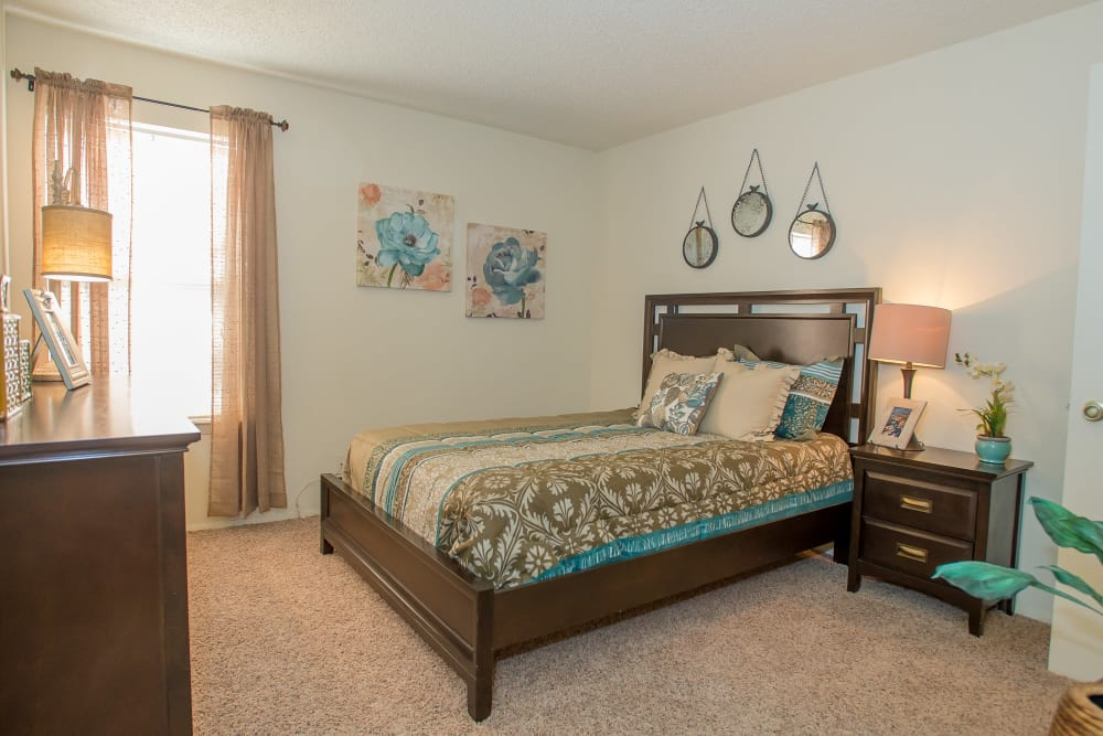 Contemporary decor in spacious master bedroom of model home at Sugarberry Apartments in Tulsa, Oklahoma