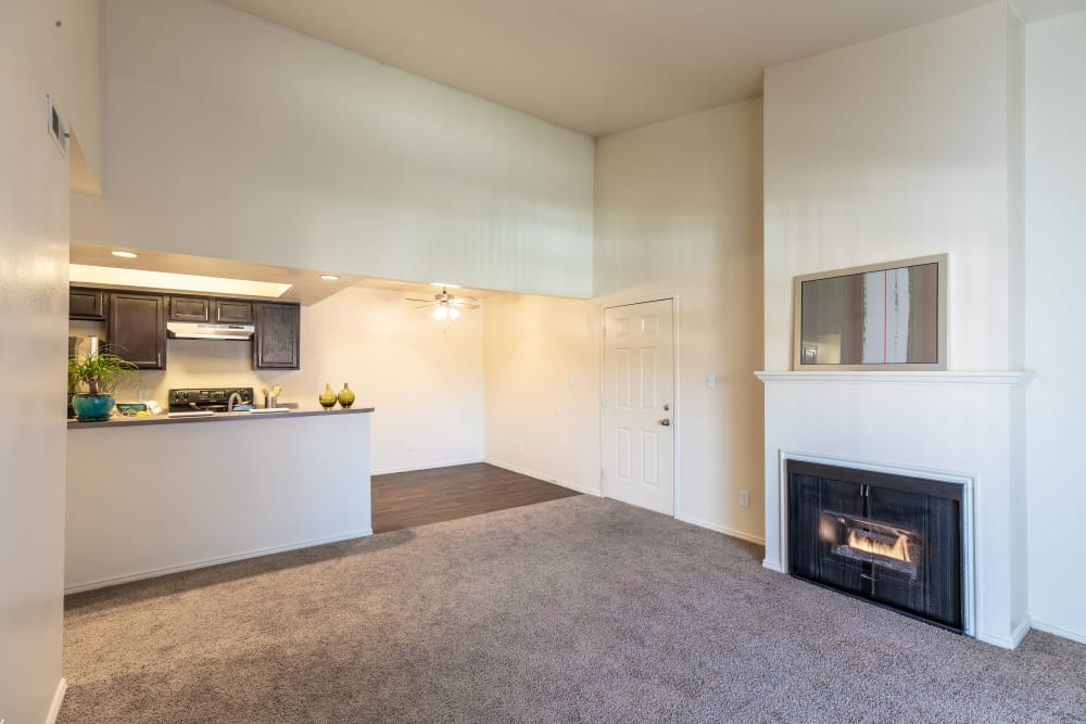 Spacious living room and fireplace with view of dining room and kitchen at Shadowbrook Apartments