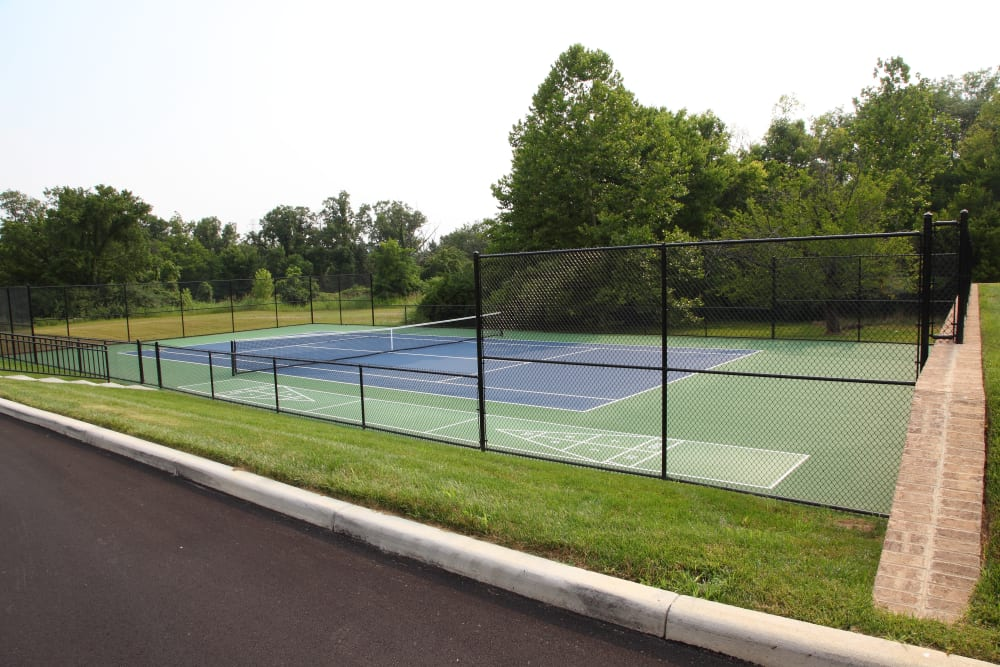 A fenced in community tennis court at The Villages at Historic Silvercrest in New Albany, Indiana