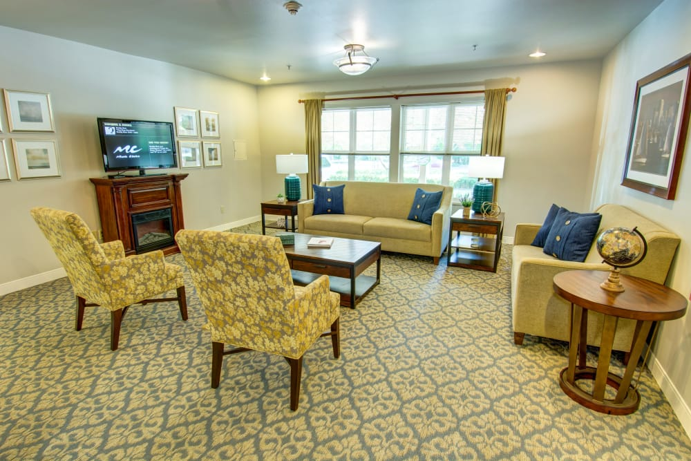 Lobby seating area with a TV at Bridgeport Place Assisted Living in University Place, Washington