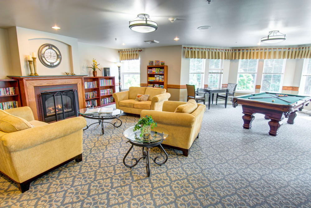 Lobby with a fireplace and pool table at Bridgeport Place Assisted Living in University Place, Washington