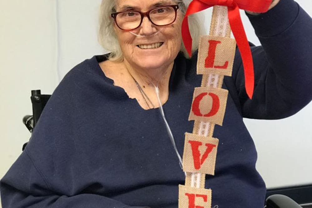 A resident holding a sign that spells love at River Terrace Health Campus in Madison, Indiana
