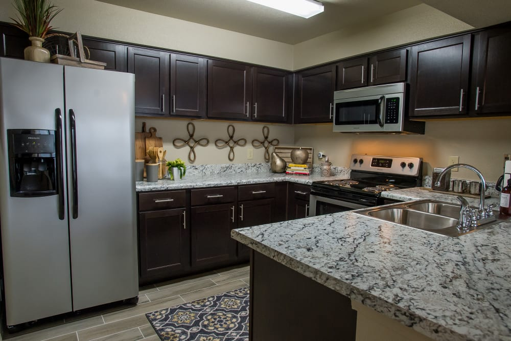 Kitchen with granite counters at Icon at Corpus Christi in Corpus Christi, Texas