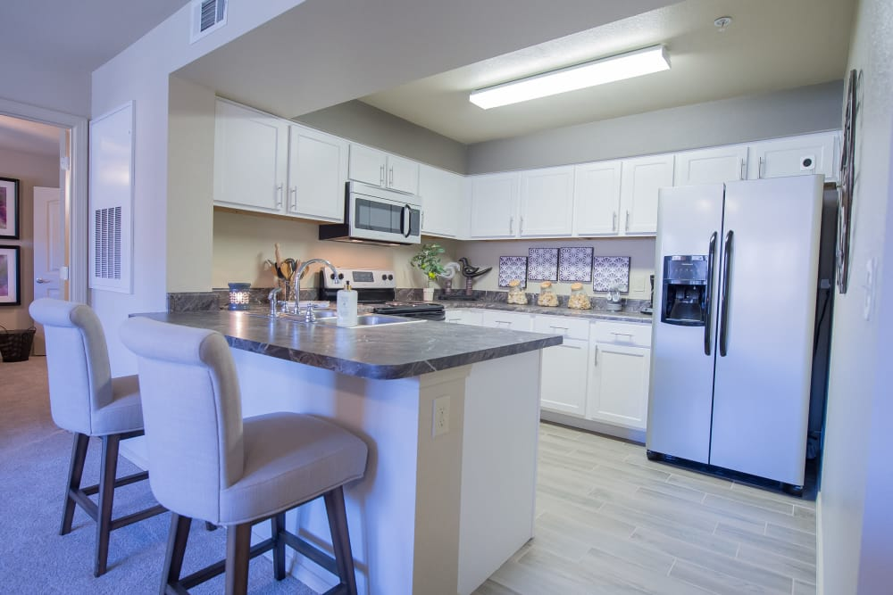Kitchen with bar seating of Mission Point Apartments in Moore, Oklahoma