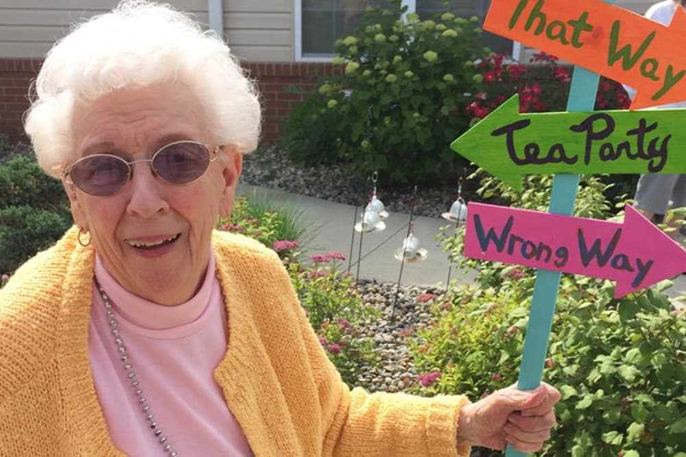 A happy resident holding an Alice in Wonderland themed sign at Bethany Pointe Health Campus in Anderson, Indiana