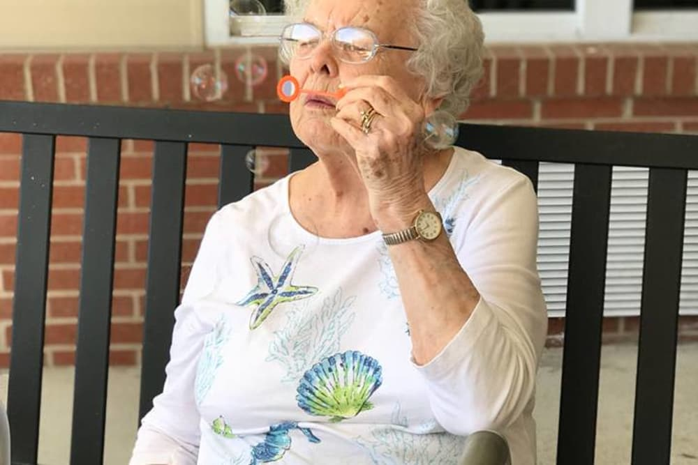 A resident blowing bubbles on the patio at Bethany Pointe Health Campus in Anderson, Indiana
