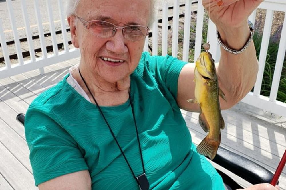 A resident posing with a fish she caught at Creasy Springs Health Campus in Lafayette, Indiana