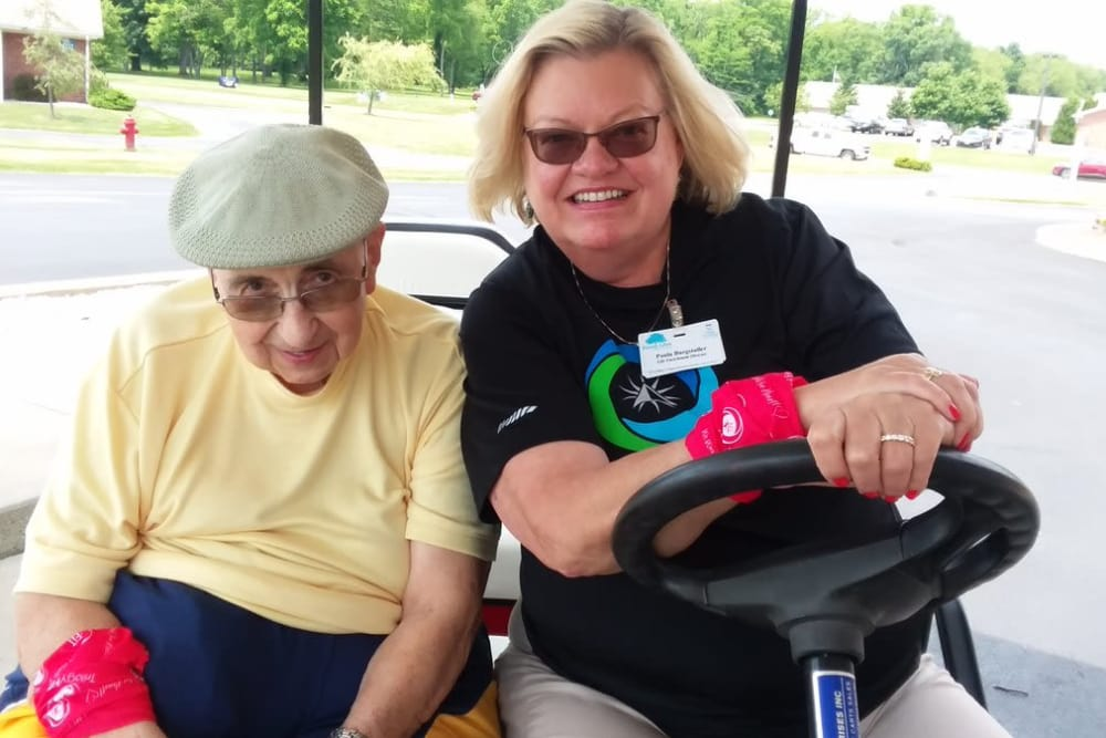 A caretaker and resident on a golf cart at Forest Glen Health Campus in Springfield, Ohio