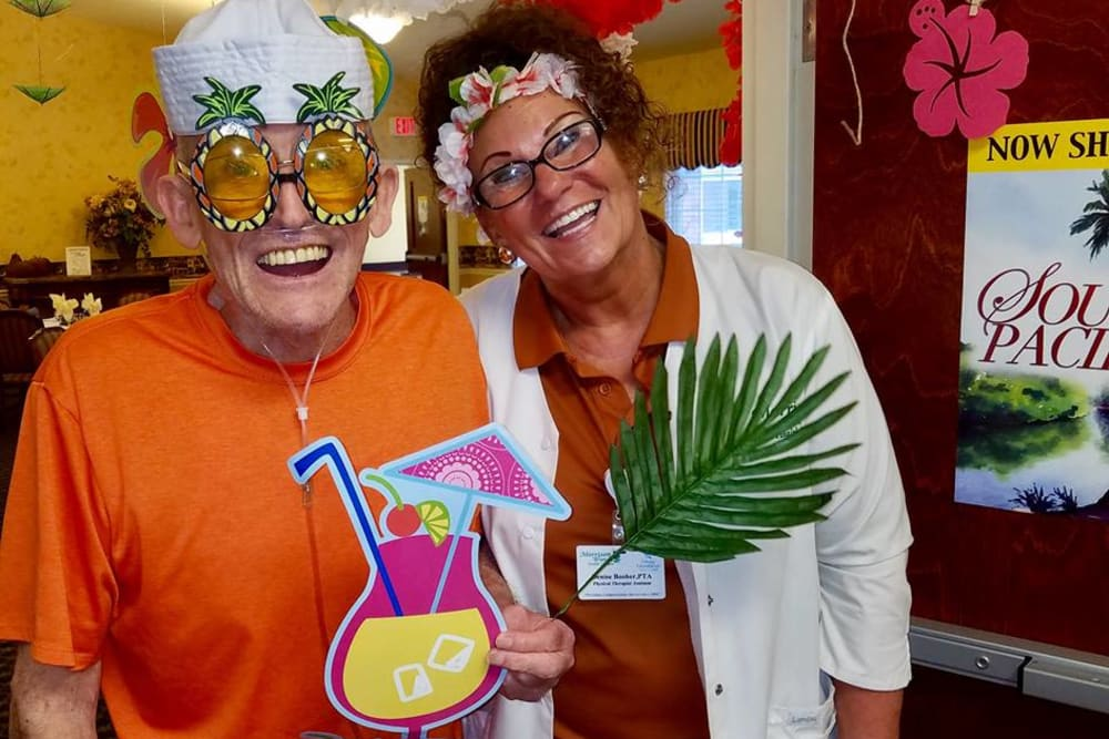 A resident and caretaker dressed up for a tropical party at Morrison Woods Health Campus in Muncie, Indiana