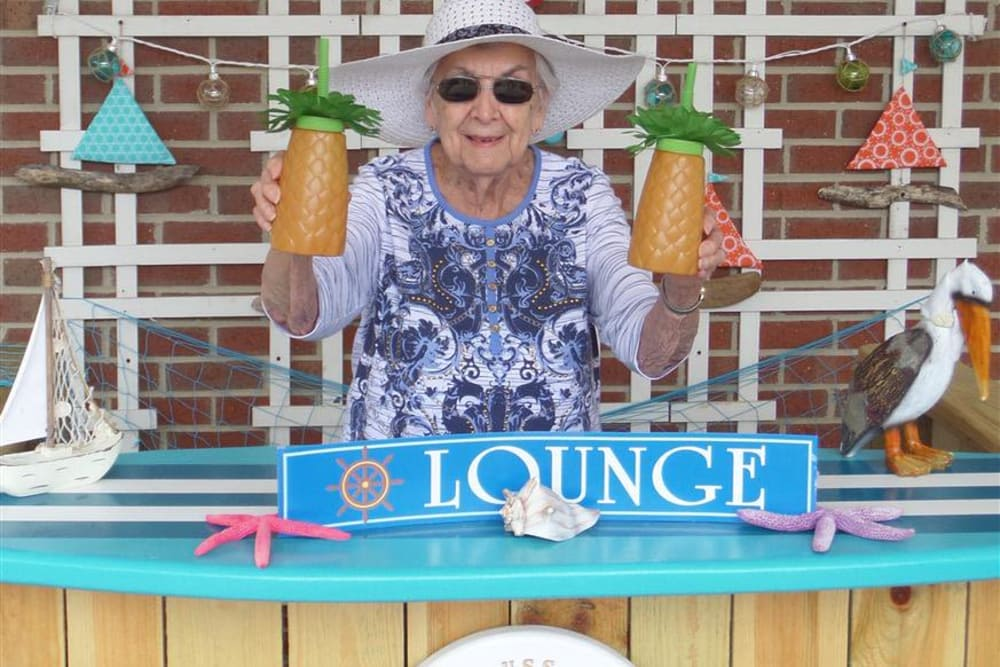 A resident holding up two drinks at a tropical themed party at Springhurst Health Campus in Greenfield, Indiana