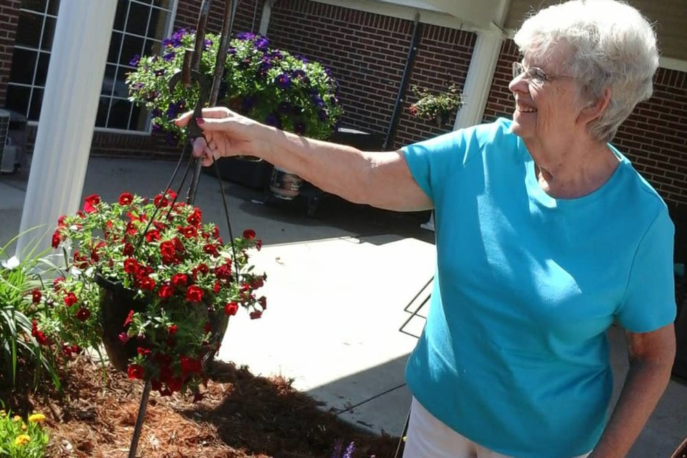 A resident hanging a pot of flowers outside at St. Charles Health Campus in Jasper, Indiana