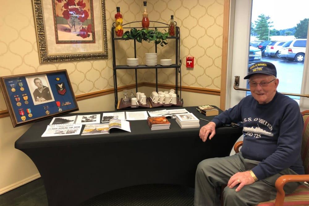 A veteran resident posing next to a memorabilia take at The Meadows of Leipsic in Leipsic, Ohio