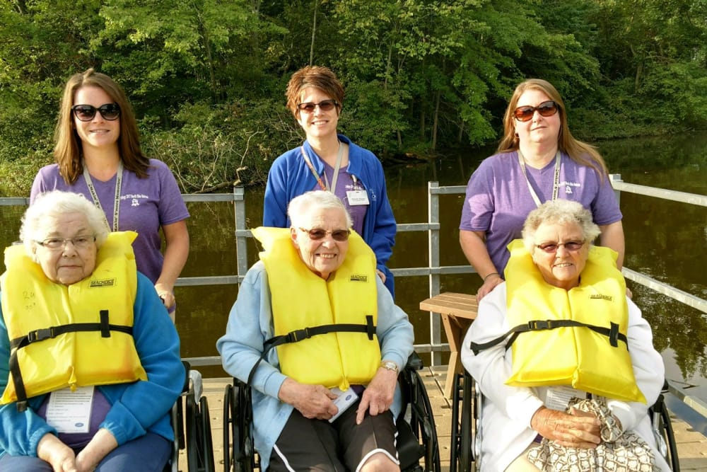 Residents with life vests and caretakers posing by the water at The Willows at Bellevue in Bellevue, Ohio
