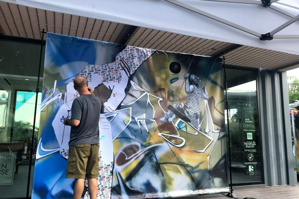 Man creating art mural near Yard 8 Midtown in Midtown Miami, Florida