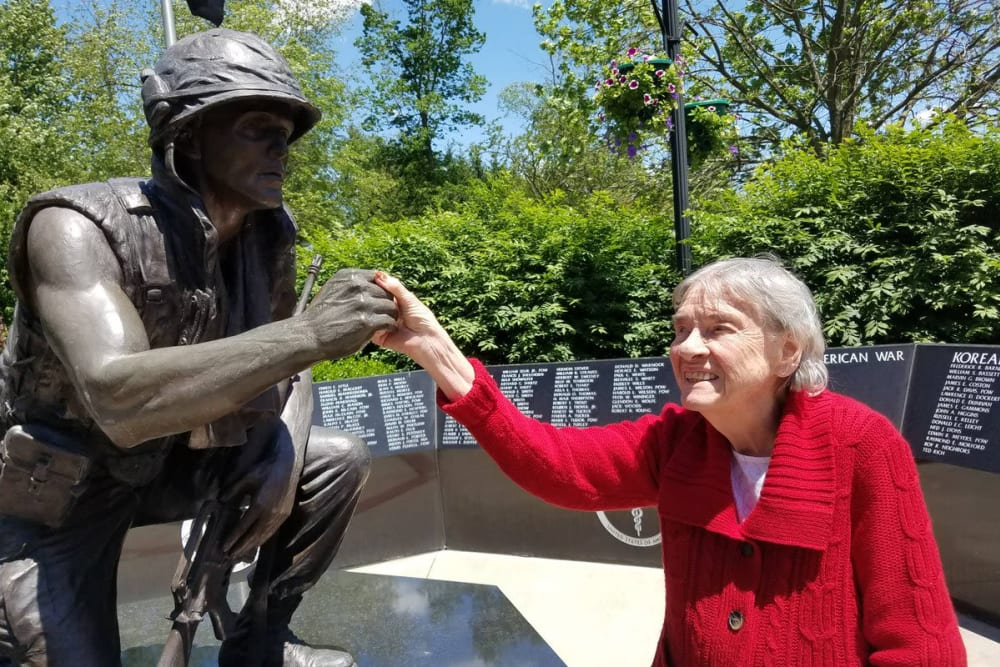 A resident from Waterford Place Health Campus in Kokomo, Indiana holding hands with a statue at a war memorial