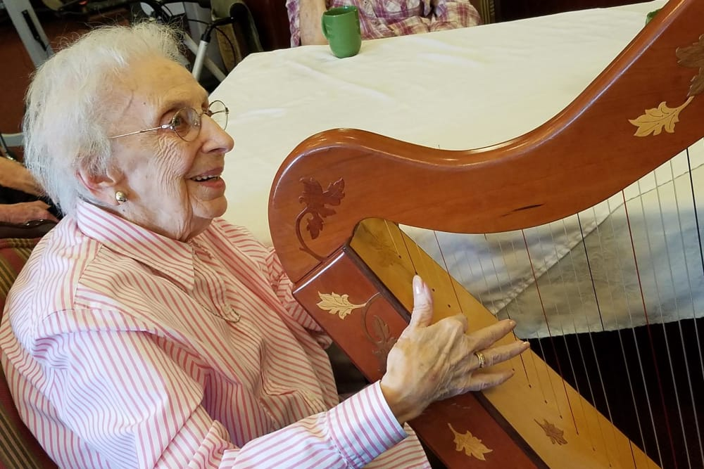 A resident playing the harp at Waterford Place Health Campus in Kokomo, Indiana