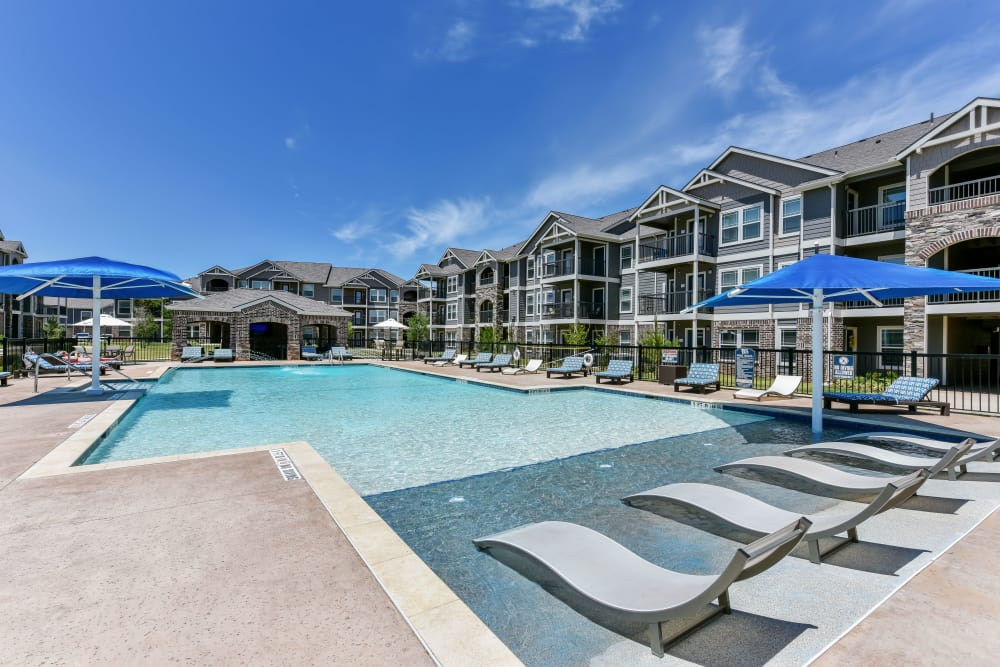 A gated community pool at Cottages at Abbey Glen Apartments in Lubbock, Texas