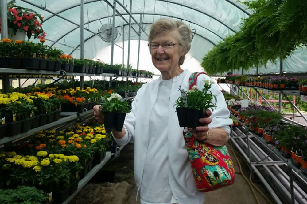 A resident from Senior Living at Forest Ridge in New Castle, Indiana in a greenhouse