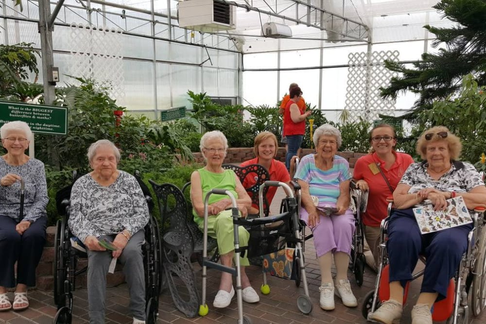 A group of residents from The Lakes of Sylvania in Sylvania, Ohio posing for a photo in a greenhouse