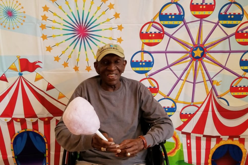 A resident with cotton candy posing in front of a backdrop at Clearvista Lake Health Campus in Indianapolis, Indiana