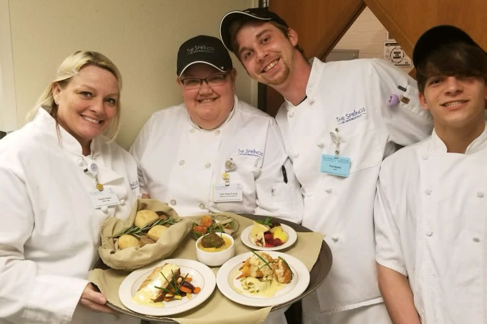 A group of chefs holding meals for residents at The Springs of Mooresville in Mooresville, Indiana