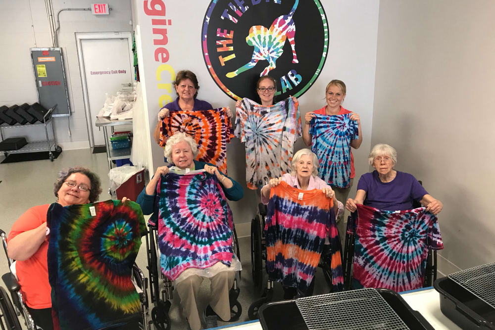 A group of residents holding tie dye shirts they made at The Springs of Mooresville in Mooresville, Indiana