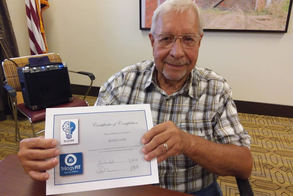 A resident holding a certificate at Wellbrooke of Crawfordsville in Crawfordsville, Indiana