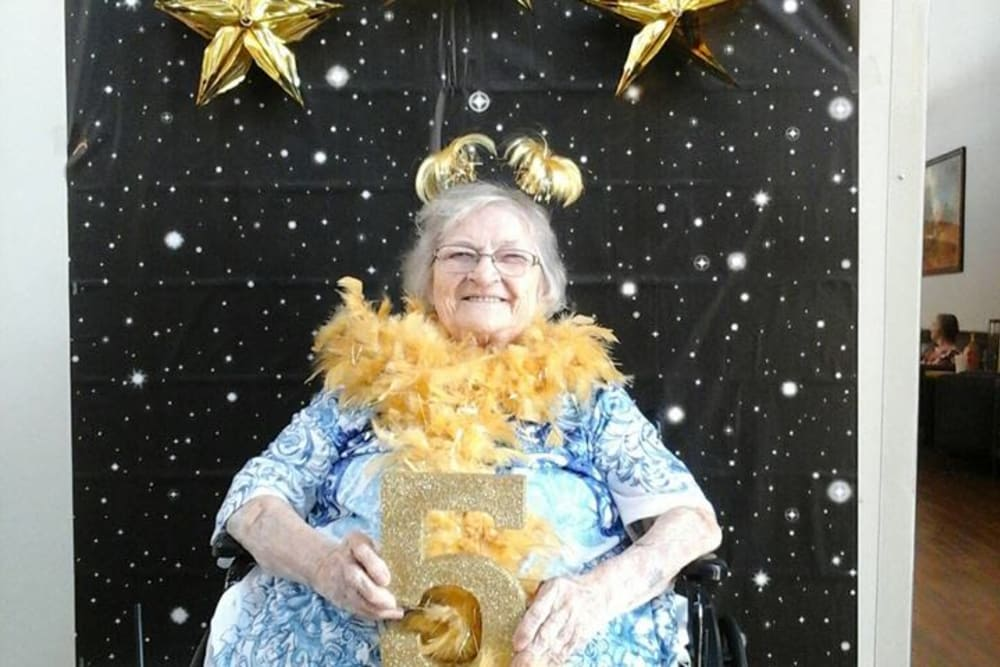 A resident holding a sparkly number five at Wellbrooke of Crawfordsville in Crawfordsville, Indiana