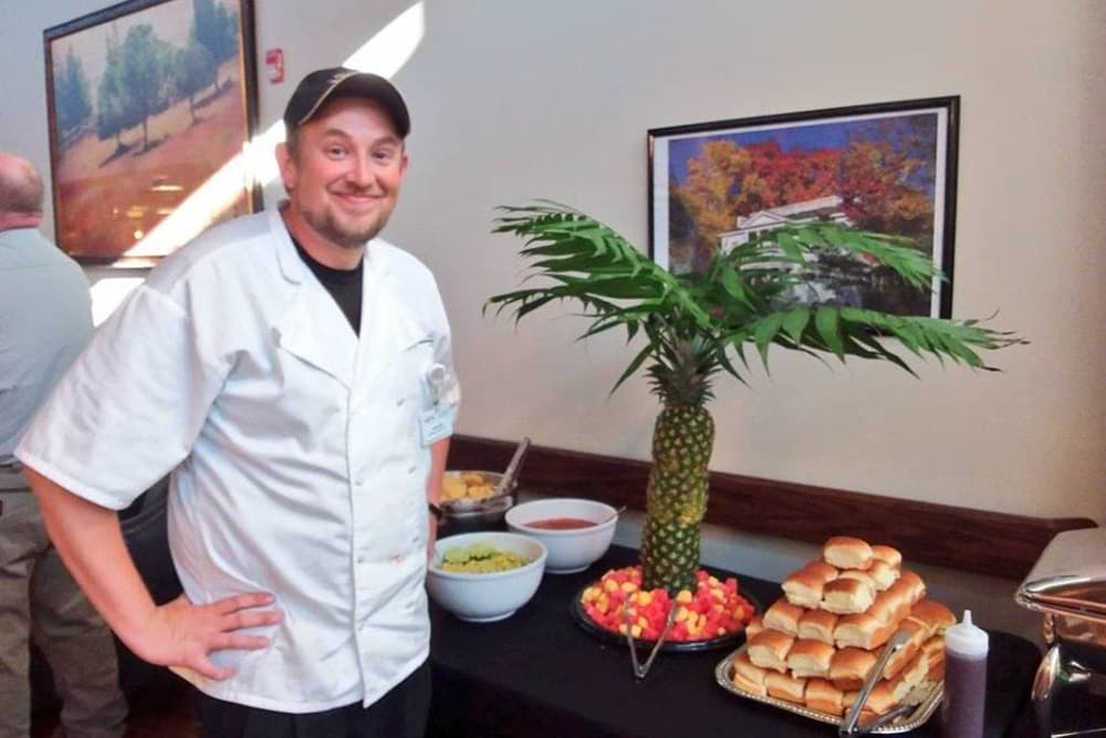 A chef posing for a photo next to the buffet at Wellbrooke of Crawfordsville in Crawfordsville, Indiana