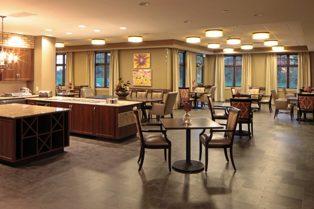 Community kitchen and dining room tables at Wellbrooke of Crawfordsville in Crawfordsville, Indiana
