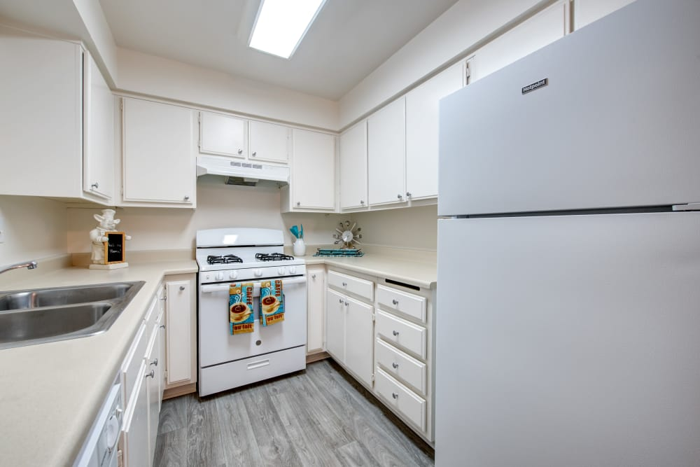 Kitchen with white appliances and matching cabinetry in apartment home at Sienna Heights Apartment Homes in Lancaster, California