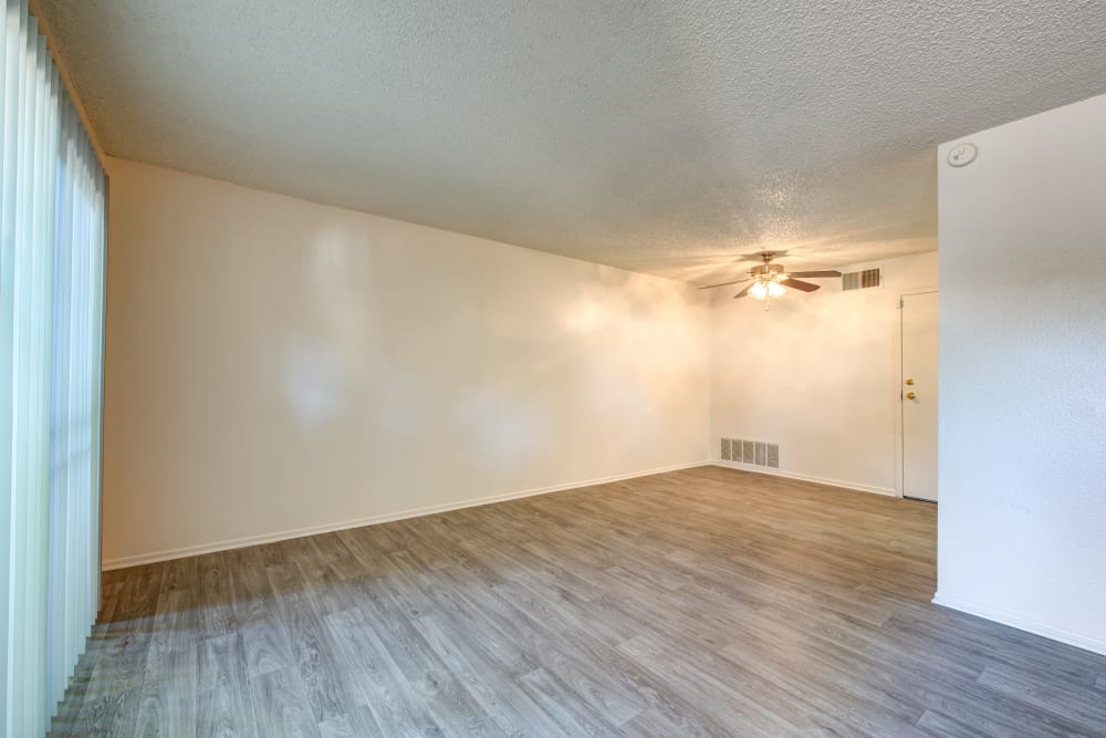 Open-concept layout with hardwood floors and ceiling fan in apartment home at Sienna Heights Apartment Homes in Lancaster, California