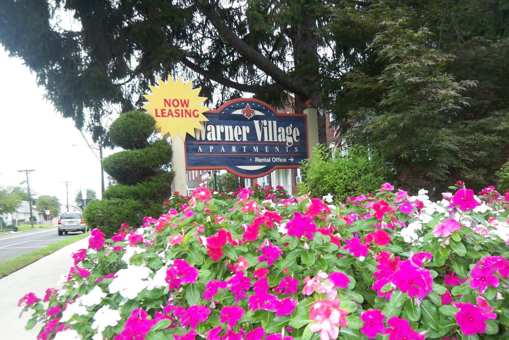 Monument sign and flowers at Warner Village Apartments in Trenton, New Jersey