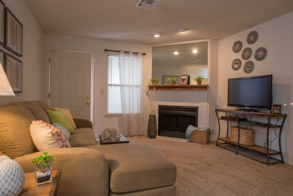 Living room with a fireplace at Polo Run Apartments in Tulsa, Oklahoma