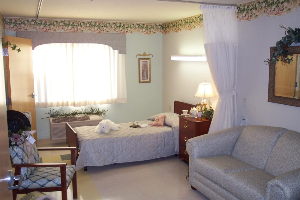 Living room and bedroom in a studio apartment at BridgePointe Health Campus in Vincennes, Indiana