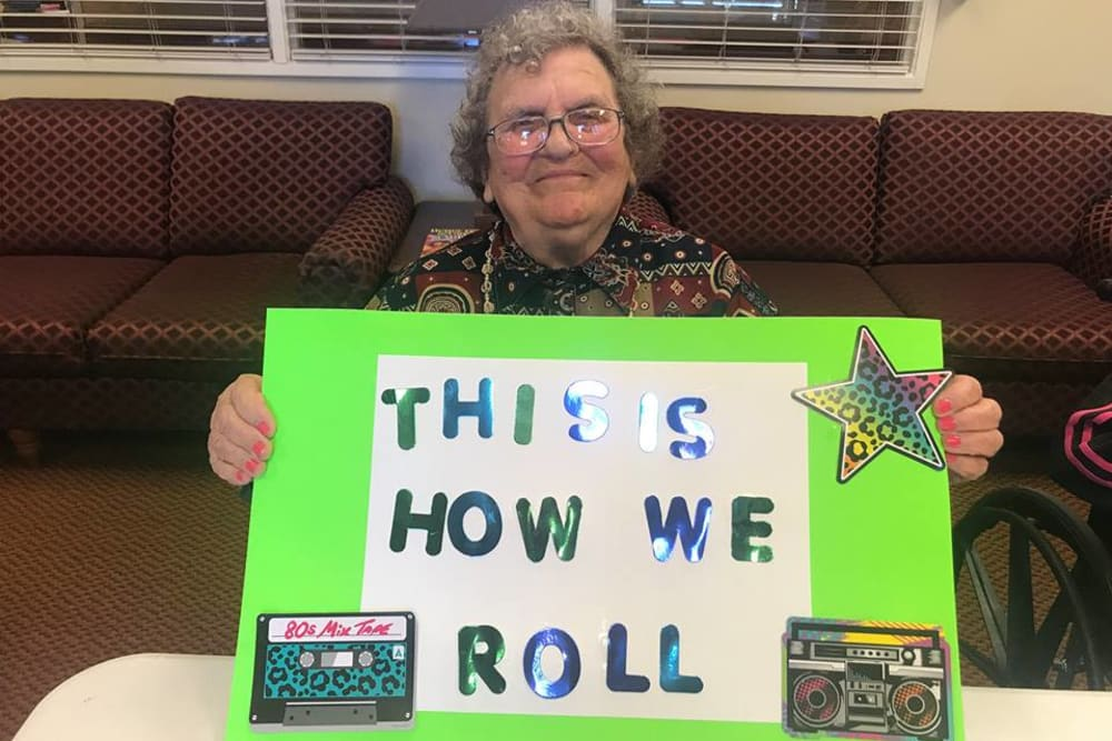 A resident holding a sign saying This is How We Roll at Cedar Ridge Health Campus in Cynthiana, Kentucky